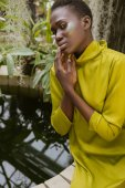 Nabídka atraktivní africká americká žena s třpytky make-up pózuje u bazénu v tropické zahradě