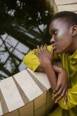 Módní africká americká dívka s třpytky make-up ve žlutých šatech pózuje u bazénu