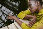 atraktivní nabídka africká americká dívka s třpytky make-up pózuje u bazénu