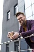 Fotografie Pohledný podnikatel ve stylu vintage oblečení usmívající se a drží šálek kávy