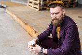 Fotografie Handsome businessman in vintage style clothes sitting on street with paper cup in hands
