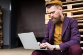 Stylish bearded businessman typing on laptop keyboard