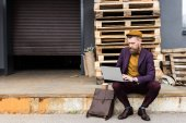 Fotografie Handsome businessman in vintage style clothes working on laptop on street