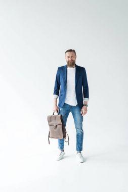 Stylish bearded man holding backpack on light background