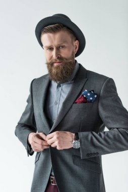 Man with vintage mustache and beard buttoning his jacket isolated on light background