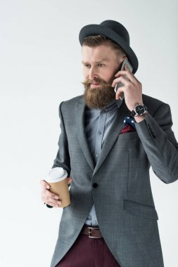 Stylish bearded businessman holding paper cup and talking on phone isolated on light background