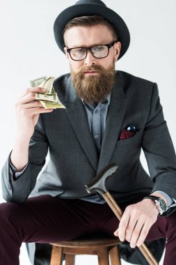 Businessman with vintage mustache and beard holding dollars isolated on light background