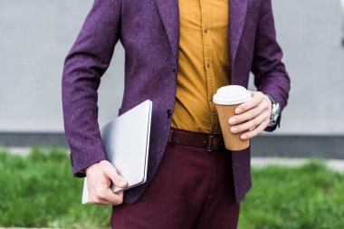 Cropped view of businessman holding laptop and paper cup