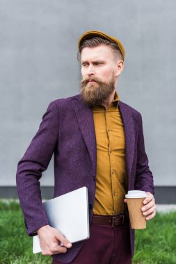 Stylish bearded businessman holding laptop and paper cup