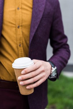 Close-up view of coffee cup in hand of stylish man