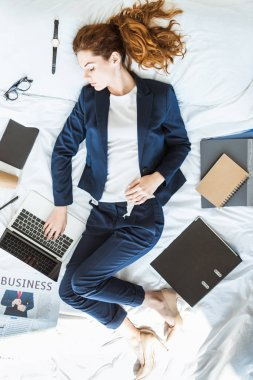 Top view of businesswoman in suit typing on laptop while lying in bed among folders and documents