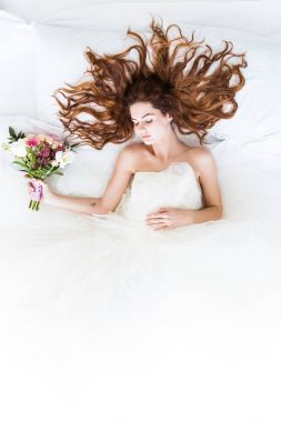 Top view of bride wearing white dress sleeping in bed with flowers bouquet