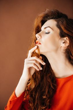 Woman with long red hair dreaming isolated on brown background
