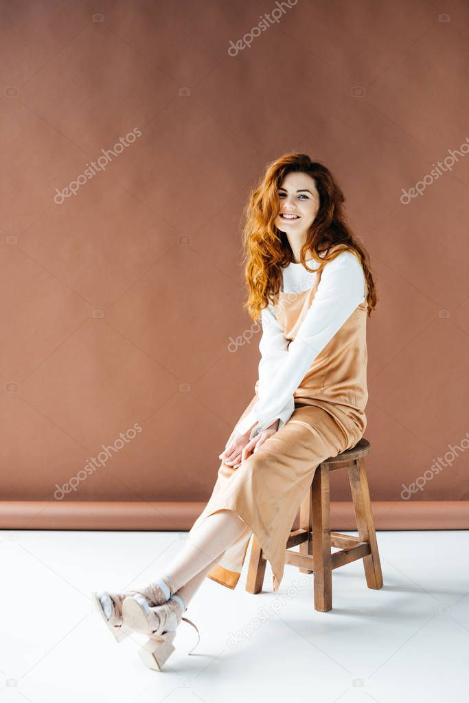 Beautiful young girl smiling and sitting on wooden stool stock vector