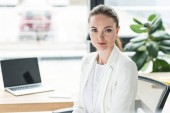 Photo portrait of smiling beautiful businesswoman in white suit at workplace with laptop in office