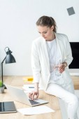 Fotografie businesswoman with glass of water working on laptop at workplace in office