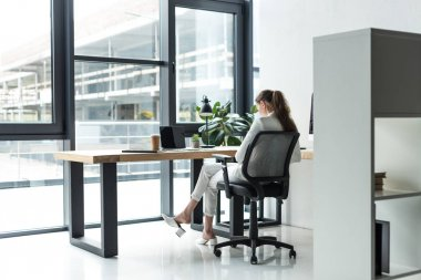 back view of businesswoman sitting at workplace in modern office