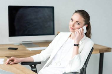 portrait of businesswoman in stylish suit talking on smartphone at workplace in office