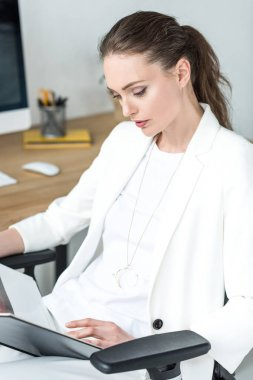 portrait of beautiful focused businesswoman reading book in office