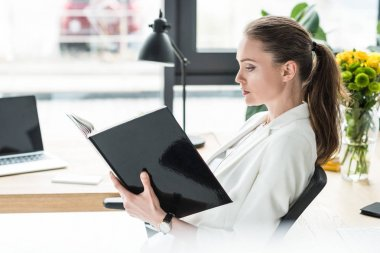 side view of beautiful businesswoman with book at workplace in office
