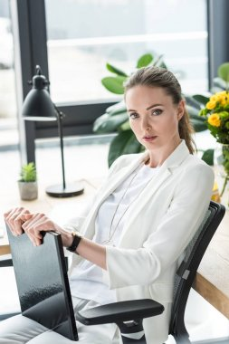 portrait of beautiful businesswoman with book at workplace in office