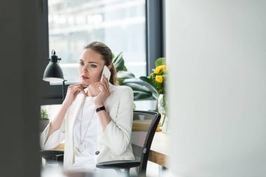 selective focus of businesswoman in stylish suit talking on smartphone at workplace in office