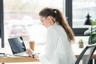 side view of focused businesswoman working on laptop at workplace in office