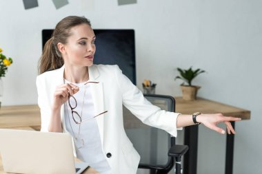 attractive businesswoman with eyeglasses at workplace with laptop in office