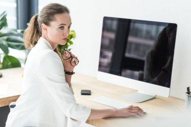 businesswoman with eyeglasses sitting at workplace with blank computer screen in office