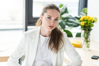 portrait of beautiful businesswoman in white suit looking at camera in office