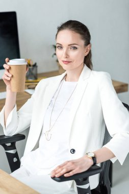 portrait of smiling businesswoman with coffee to go sitting at workplace in office