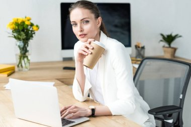 portrait of businesswoman with coffee to go at workplace with laptop in office