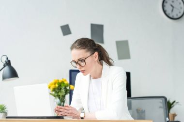 portrait of businesswoman in eyeglasses working on laptop at workplace in office