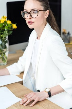 portrait of pensive businesswoman in eyeglasses at workplace in office