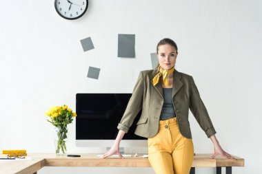 beautiful businesswoman in fashionable clothing leaning on workplace with computer screen and bouquet of flowers in vase in office