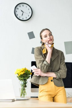 attractive stylish businesswoman holding eyeglasses and smartphone, looking at camera in office