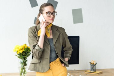 beautiful stylish businesswoman talking by smartphone and looking away in office