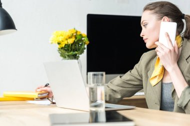 beautiful businesswoman talking by smartphone and taking notes while working in office