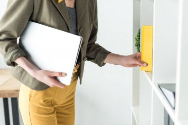 cropped shot of businesswoman holding laptop and taking book from shelf in office