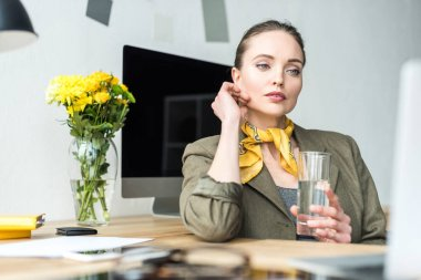 beautiful pensive businesswoman holding glass of water and looking away in office