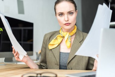 serious stylish businesswoman holding papers and looking at camera in office