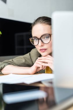 selective focus of beautiful businesswoman in eyeglasses looking at camera at workplace