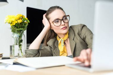 attractive stylish businesswoman in eyeglasses using laptop at workplace