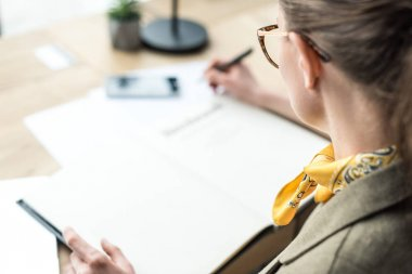 cropped shot of businesswoman in eyeglasses taking notes at workplace