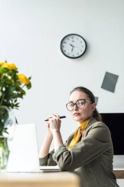 beautiful middle aged businesswoman in eyeglasses using laptop and looking at camera in office