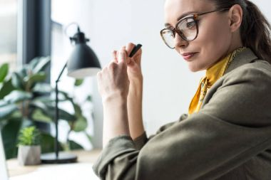 side view of beautiful buisnesswoman in eyeglasses sitting at workplace