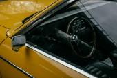 Fotografia vista ravvicinata della rotella di direzione dellautomobile retrò giallo