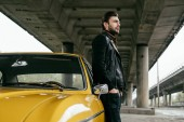 Fotografie side view of stylish man standing near yellow retro car and looking away