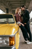 Fotografie side view of beautiful sensual young couple hugging while leaning at yellow car
