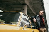 Fotografie handsome stylish young man in leather jacket leaning at retro car and looking away